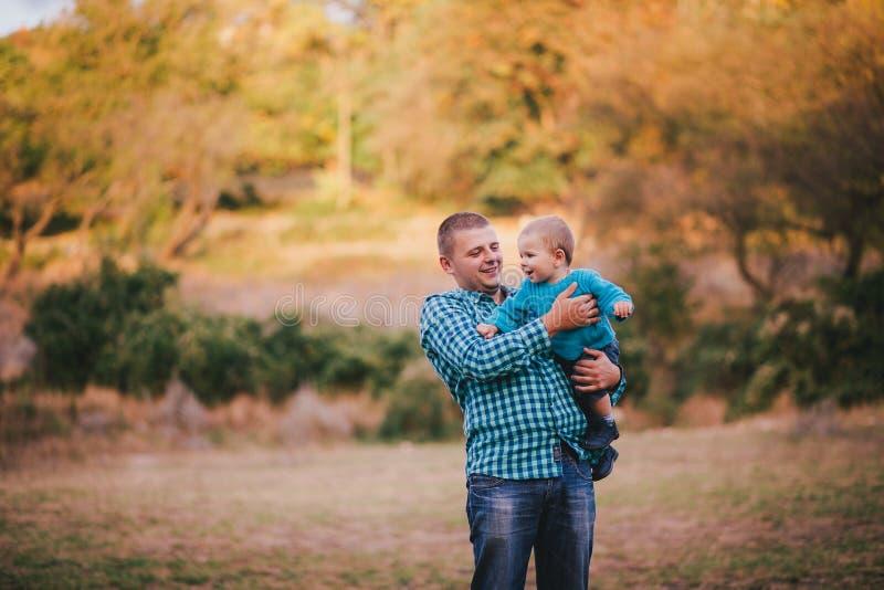Будьте отцом и его маленький сын идя в лес осени стоковое изображение rf
