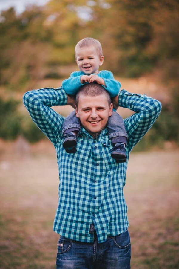 Будьте отцом и его маленький сын идя в лес осени стоковая фотография rf
