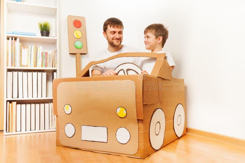 Будьте отцом и его сын управляя handmade автомобилем картона стоковые фото