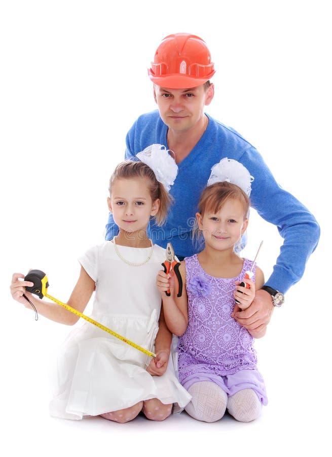 Будьте отцом объятий 2 шлема его дочерей стоковое фото rf