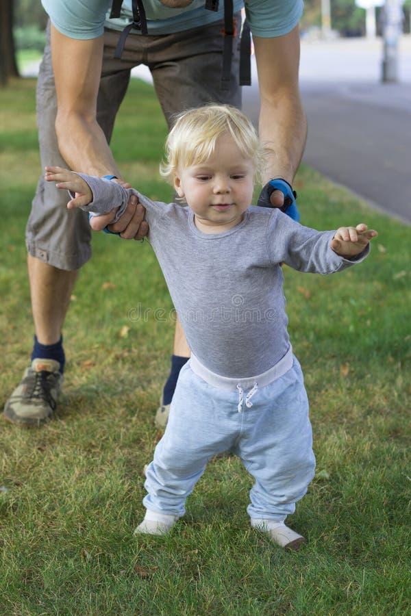 Будьте отцом ограничивать их младенца, малыша уча идти стоковые изображения