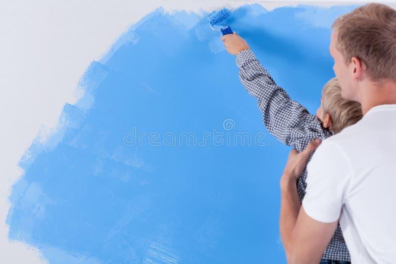 Будьте отцом поднимать его сына во время красить стену стоковое изображение