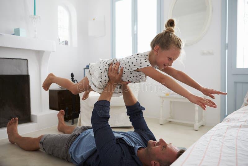 Будьте отцом поднимаясь дочери в воздух внутри помещения стоковая фотография