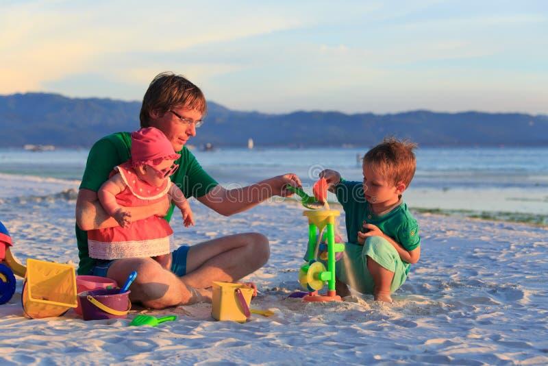 Будьте отцом при 2 дет играя на пляже песка стоковое фото rf