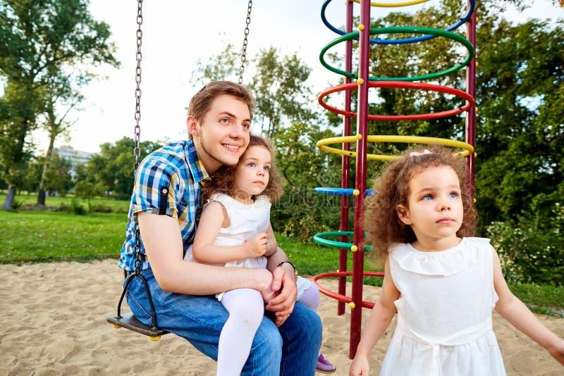 Будьте отцом с детьми на качании на спортивной площадке стоковое изображение