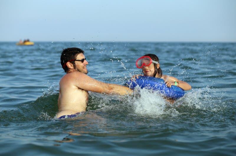 Будьте отцом с заплывами дочери в воде моря стоковое фото