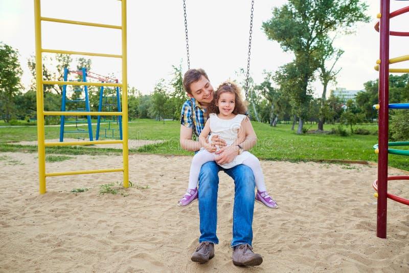 Будьте отцом с ребенком на качании на спортивной площадке стоковая фотография rf