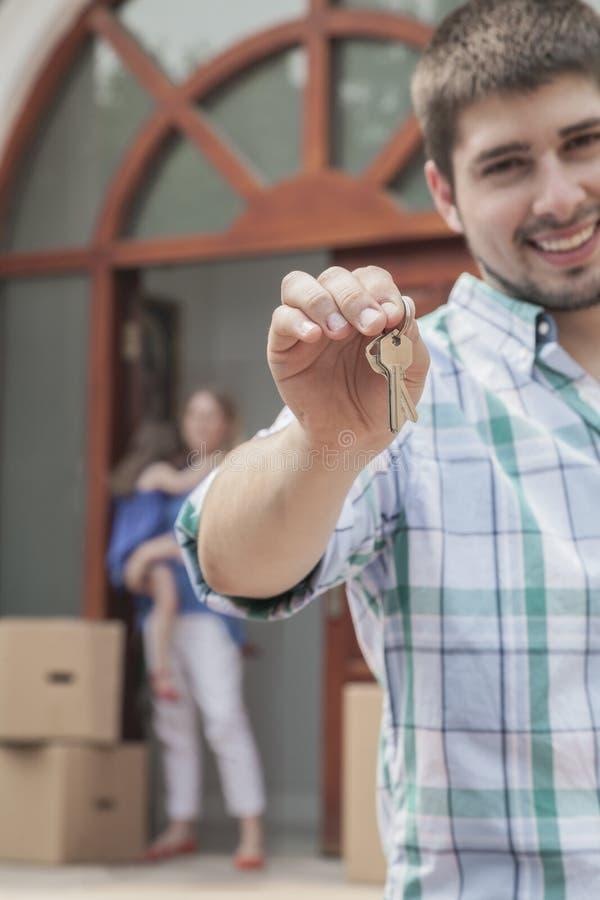 Будьте отцом усмехаться и держать ключи к новому дому, семье на заднем плане стоковая фотография rf