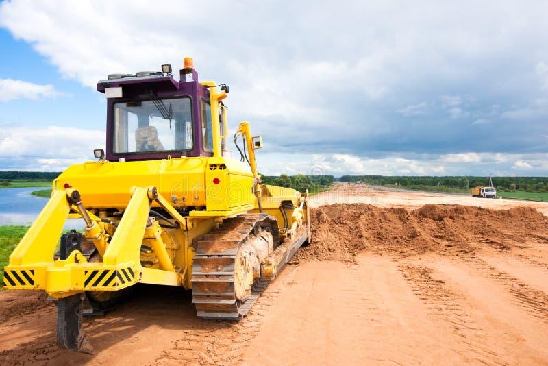 Бульдозер во время дорожных работ конструкции стоковое фото rf