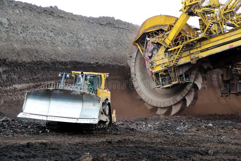 Бульдозер и огромный экскаватор минирования катят внутри угольную шахту бурого угля стоковая фотография rf