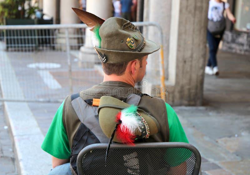 Бывший солдат сидя и показывая его заднее во время воинской итальянской национальной встречи стоковая фотография