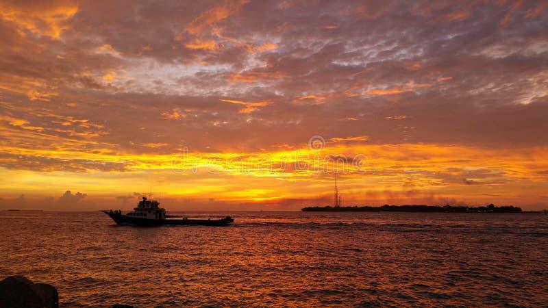 Быстроходный катер идя медленно на красивый заход солнца стоковые фотографии rf