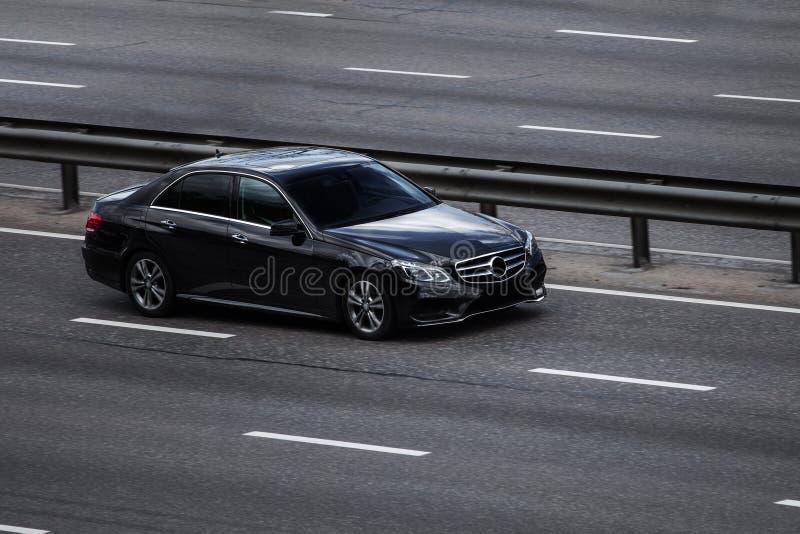 Быстро проходить benz e Мерседес черный на пустом шоссе стоковые изображения rf