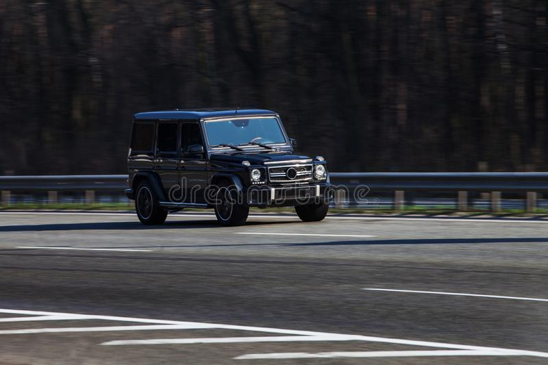 Быстро проходить g Wagen benz Мерседес черный на пустом шоссе стоковое фото
