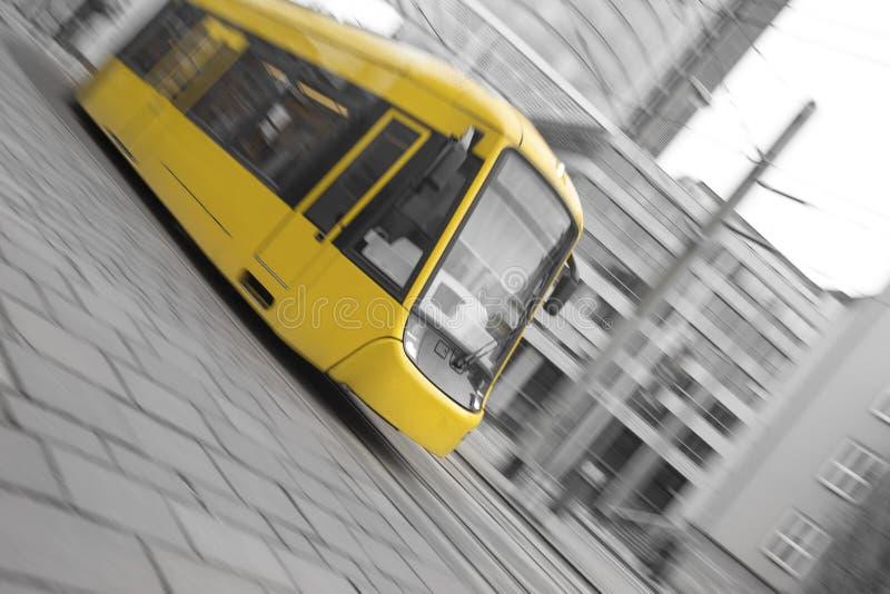 быстро проходя желтый трамвай с черно-белой предпосылкой города стоковые фото