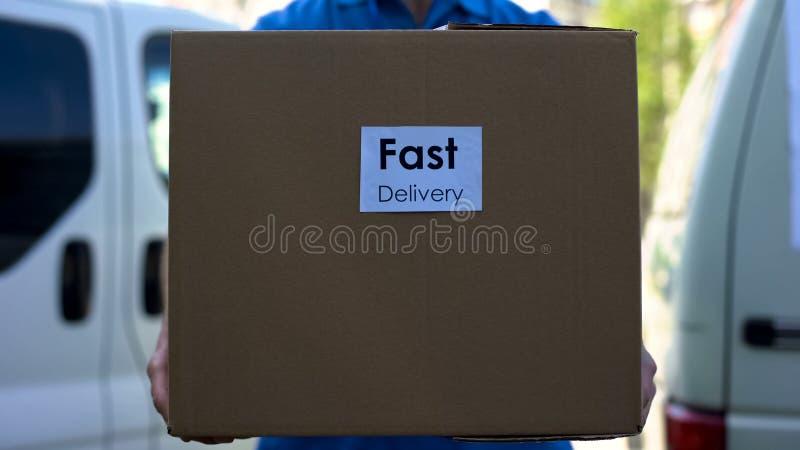 Быстрый курьер обслуживания поставки в равномерной держа картонной коробке, срочной доставке стоковое изображение rf