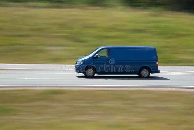 Быстрый управляя голубой автомобиль минифургона стоковое фото rf