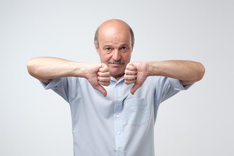 Быть в дурном настроении зрелый кавказский человек показывая его нелюбовь и разочарование с большими пальцами руки вниз на передн стоковое изображение