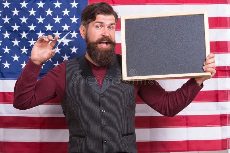 Быть мастерским парикмахером Barbering парикмахера уча на предпосылке американского флага Бородатый парикмахер держа ножницы и стоковое фото