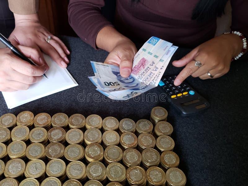 бюджет и администрация, руки человека 2 считая монетки и мексиканские банкноты стоковое изображение rf