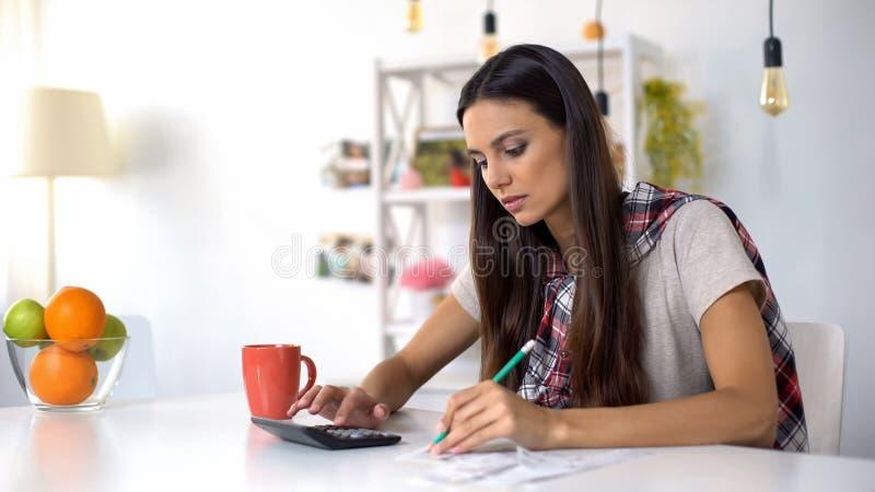 Бюджет милой дамы планируя домашний, считающ доходы и расходы, сохраняя деньги стоковые фото