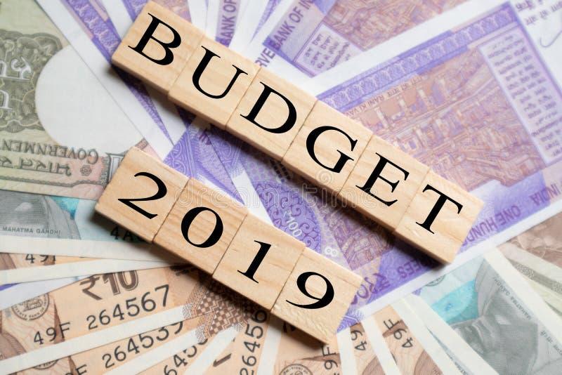 Бюджет 2019 напечатанный на деревянных печатных буквах с новыми индийскими примечаниями валюты как предпосылка стоковые изображения rf