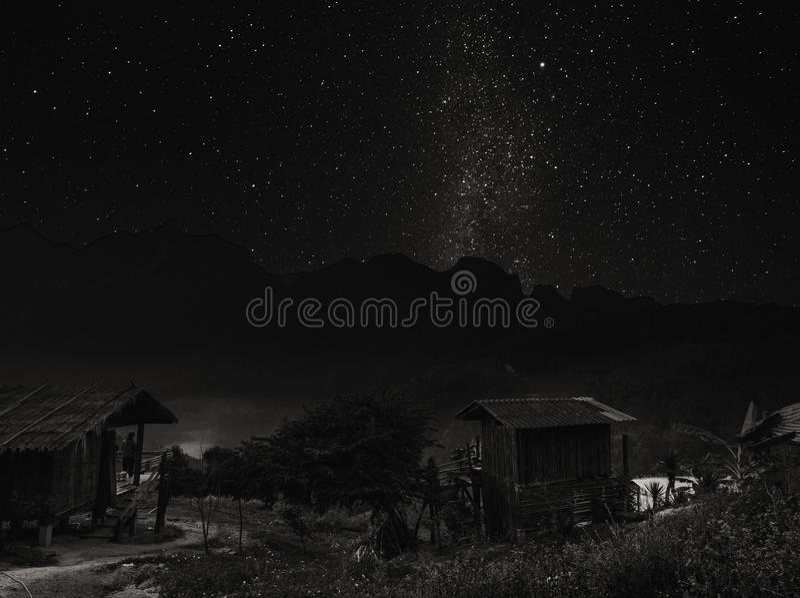 Благоустраивайте сельский район на горе на ноче с ясным небом полным звезд, в Таиланде, черно-белом стоковое изображение