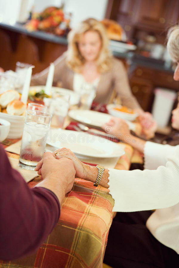 Благодарение: Семья говорит молитву перед обедающим благодарения стоковое изображение