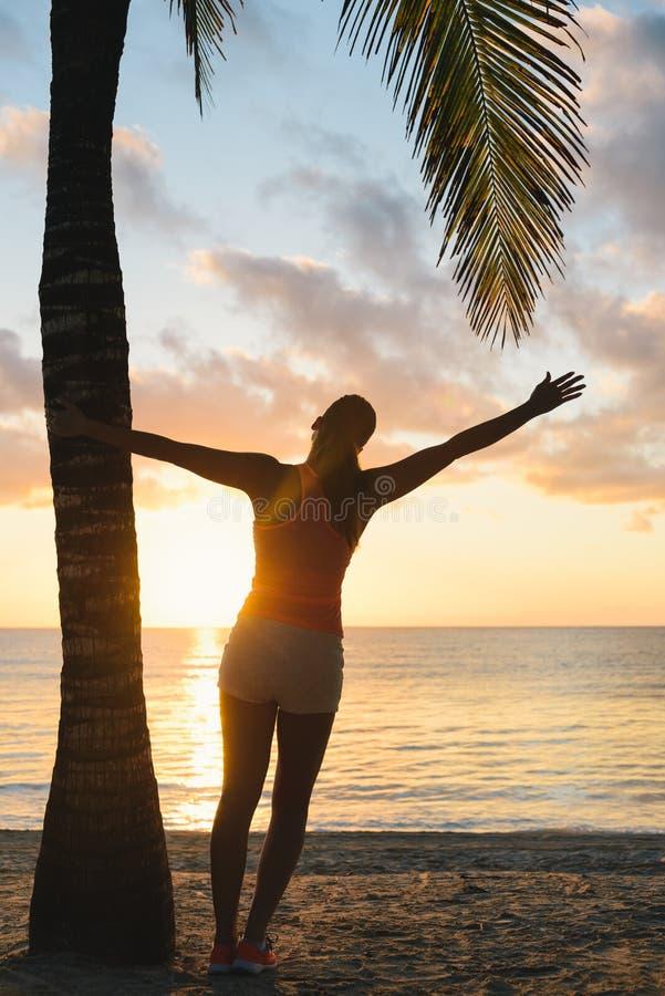 Блаженная женщина фитнеса наслаждаясь разминкой захода солнца пляжа под ладонями стоковые изображения