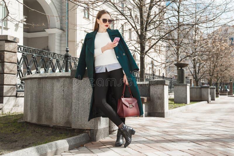 Блестящая девушка одела в дорогом пальто, белом свитере и солнечных очках с мобильным телефоном в ее представлять руки стоковые изображения rf