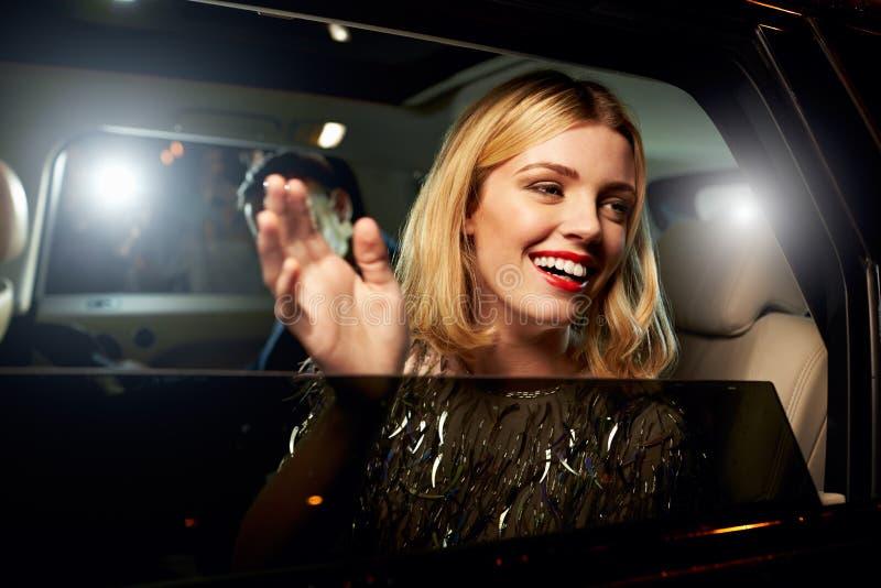 Блестящая женщина развевая через окно лимузина стоковое изображение