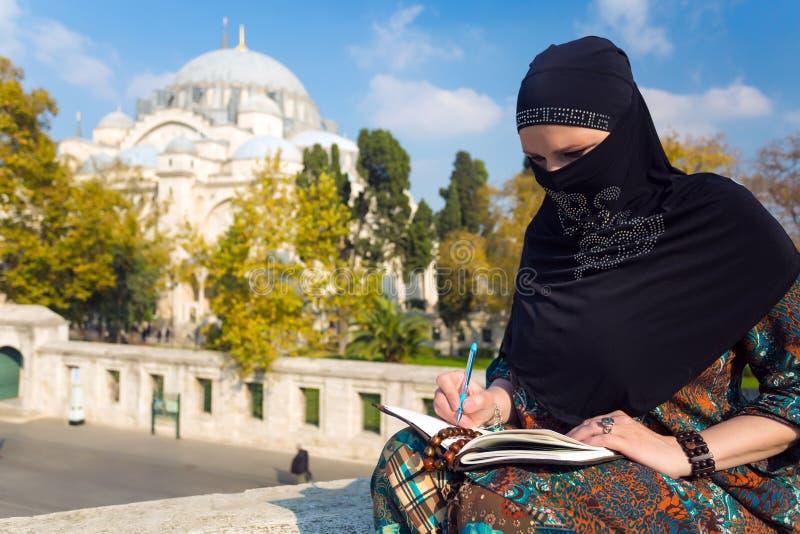 Ближневосточный эскиз чертежа женщины в бумажном блокноте с карандашем стоковое изображение