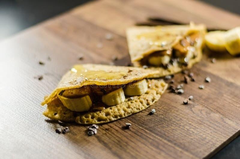 Блинчики банана с обломоками Choco на таблице стоковое фото
