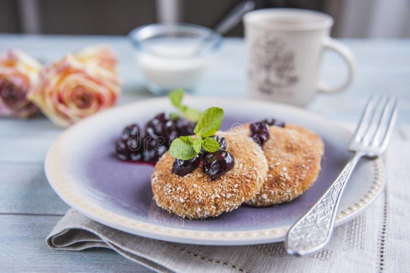 Блинчики сыра творога, чизкейки для завтрака с ягодами и сметана стоковые фотографии rf