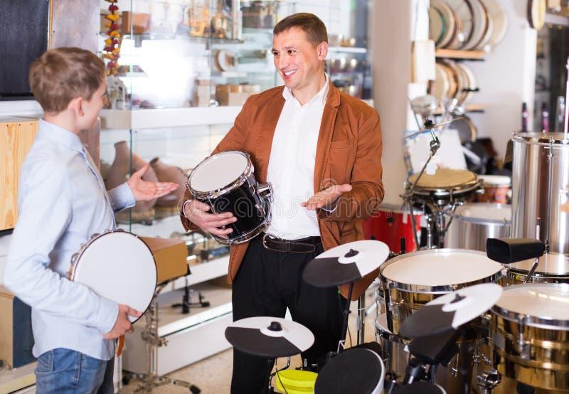 Блоки барабанчика отца и сын-подростка рассматривая в магазине гитары стоковые изображения