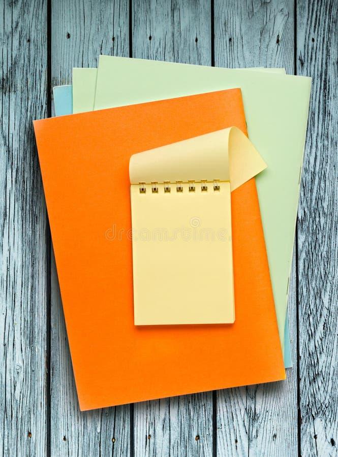 Блокноты на деревянной предпосылке стоковые изображения rf