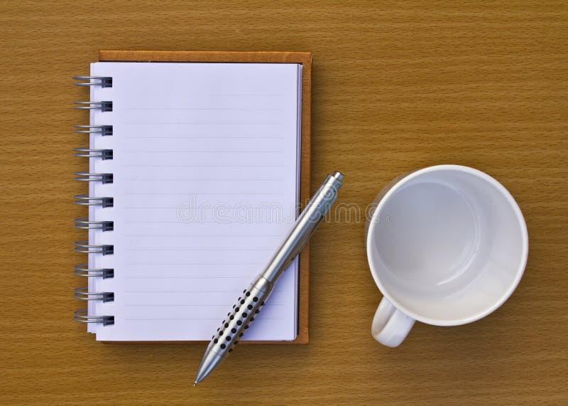 Блокнот и ручка и кофейная чашка и камера. стоковое изображение