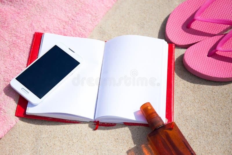 Блокнот и умный телефон на пляже стоковые изображения rf