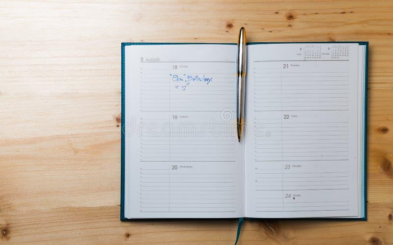 Блокнот календаря на деревянной предпосылке стоковое изображение