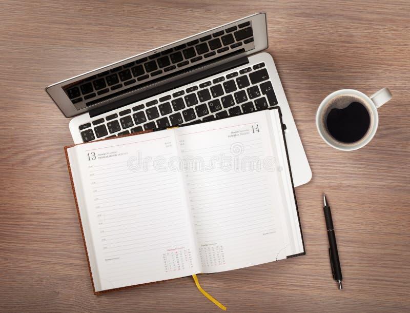 Блокнот, компьтер-книжка и кофейная чашка на деревянной таблице стоковое изображение