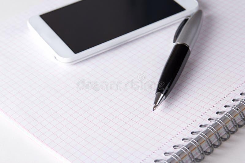 Блокнот с проверенными страницами, ручкой и умным телефоном стоковые изображения rf
