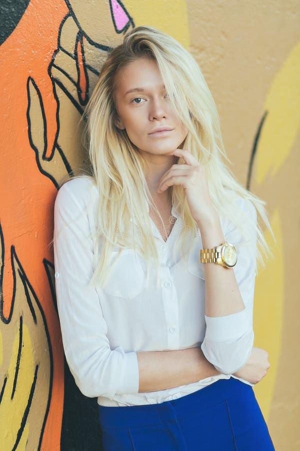 Блондинка девушки с длинными волосами, против граффити стены стоковая фотография