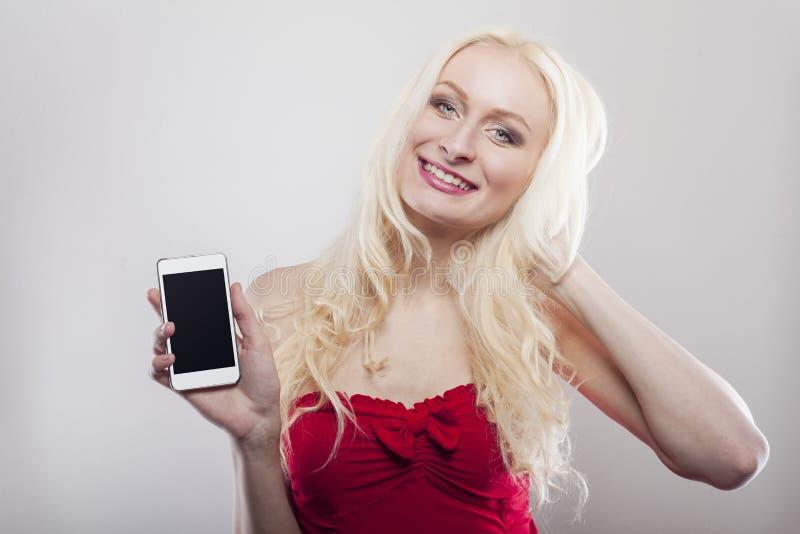 Блондинка держа белый сотовый телефон в ее руках стоковое изображение rf