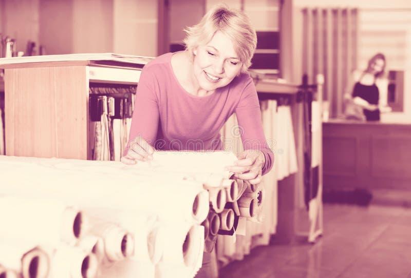 Блондинка постарела клиент женщины ища красивая ткань в texti стоковое изображение rf
