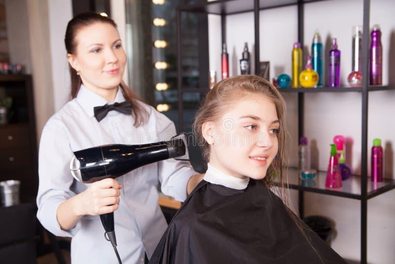 Блондинка суша волос парикмахера в салоне стоковое фото rf