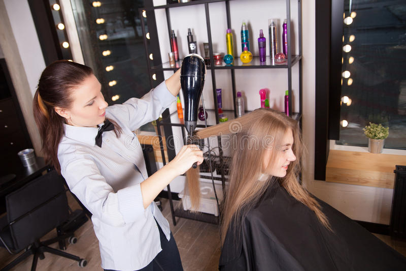 Блондинка суша волос парикмахера в салоне стоковые фотографии rf