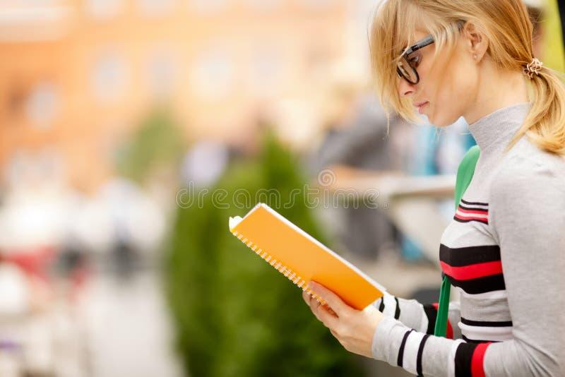 Блондинка с книгой чтения стекел на улице стоковые фотографии rf