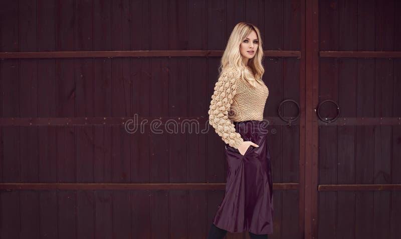 Блондинка Georgeous элегантная в ярком платье на деревянной предпосылке стоковая фотография rf