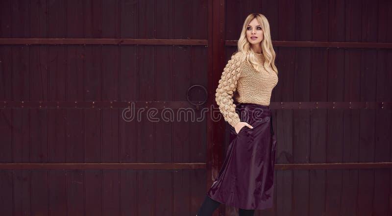 Блондинка Georgeous элегантная в ярком платье на деревянной предпосылке стоковые фотографии rf