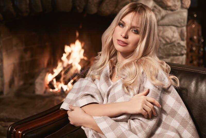 Блондинка Georgeous элегантная под яркой шотландкой около камина стоковое фото rf
